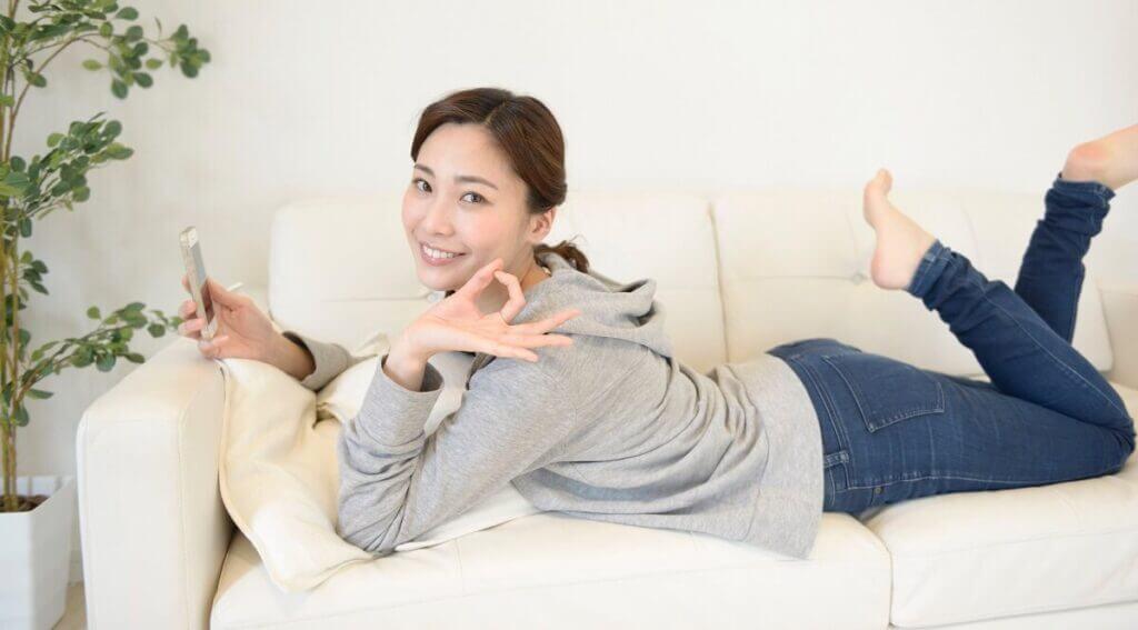 スマホを持ちソファに寝転びOKサインをしている女性