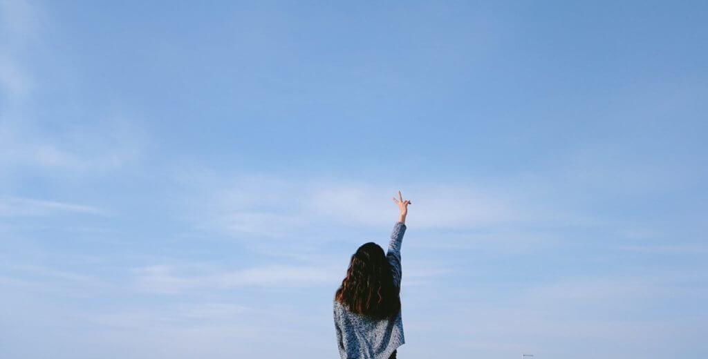 青空にピースする女性